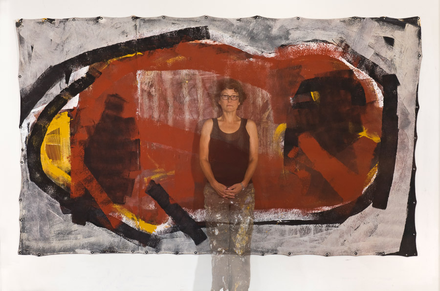 Barbara Downs standing with her painting Inward, Acrylic/Mixed-Media on Unstretched Canvas