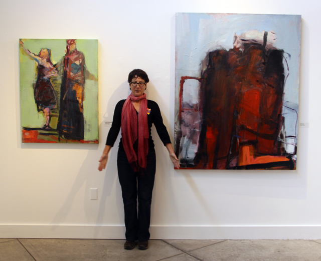 Barbara Downs standing in front of her paintings
