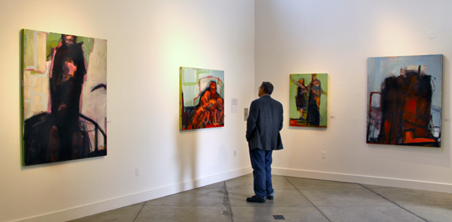 Tom Maderos viewing the paintings of Barbara Downs